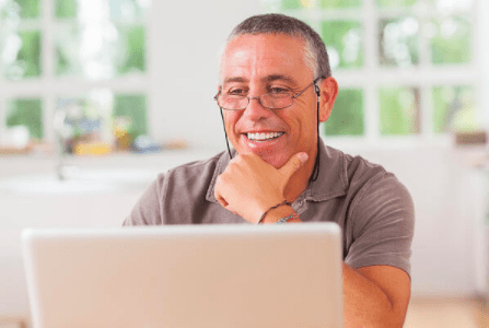 Older man at kitchen table on laptop virtual training