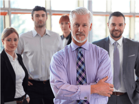 Older Man in front of his sales team in office