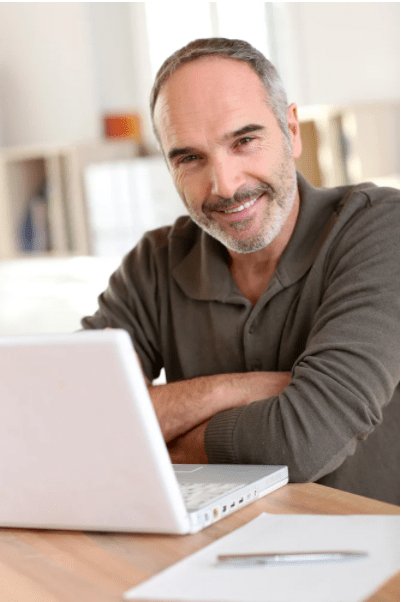 Smiling mIddle age man at desk with laptop